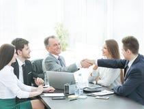 L'uomo d'affari e l'investitore stringono le mani al tavolo delle trattative immagini stock