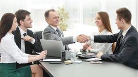 L'uomo d'affari e l'investitore stringono le mani al tavolo delle trattative immagini stock libere da diritti