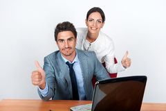 L'uomo d'affari e la donna di affari mostrano il gesto di mano nel posto di lavoro immagini stock