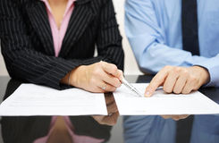 L'uomo d'affari e la donna di affari stanno indicando l'articolo del TR Immagini Stock