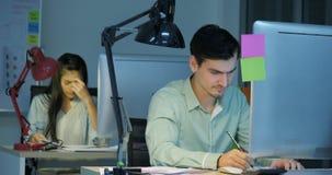 L'uomo d'affari e la donna di affari stanchi e sollecitati stanno lavorando tardi nella notte video d archivio