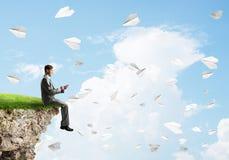 L'uomo d'affari elegante sul bordo della roccia che fa le chiamate e la carta spiana il volo intorno immagine stock libera da diritti