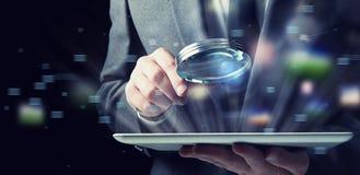 L'uomo d'affari esamina una compressa con una lente d'ingrandimento Concetto di sicurezza di Internet fotografie stock