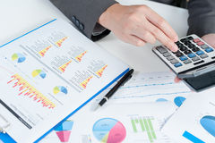 L'uomo d'affari facendo uso del calcolatore analizza il rapporto Immagine Stock