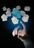 L'uomo d'affari facendo uso di 3D ha reso le piccole case bianche e blu Immagini Stock