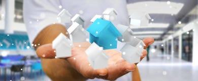 L'uomo d'affari facendo uso di 3D ha reso le piccole case bianche e blu Immagine Stock Libera da Diritti
