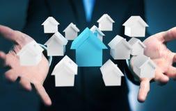 L'uomo d'affari facendo uso di 3D ha reso le piccole case bianche e blu Fotografia Stock Libera da Diritti