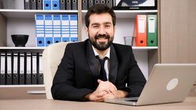 L'uomo d'affari felice che scrive una risposta a macchina poi esamina la macchina fotografica e sorride stock footage