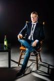 L'uomo d'affari felice che tiene vetro di whiskey e degli sguardi nella macchina fotografica Colpo dello studio fotografia stock libera da diritti