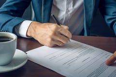L'uomo d'affari firma i documenti giuridici importanti sul desktop con la tazza di caffè Fotografia Stock Libera da Diritti