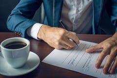 L'uomo d'affari firma i documenti giuridici importanti sul desktop con la tazza di caffè Immagine Stock