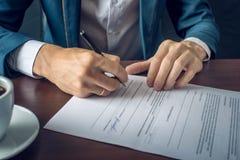 L'uomo d'affari firma i documenti giuridici importanti sul desktop con la tazza di caffè Immagini Stock Libere da Diritti
