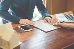 L'uomo d'affari firma il contratto dietro il modello architettonico domestico Discussione con uno stafflocativo della società d fotografia stock libera da diritti