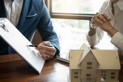 L'uomo d'affari firma il contratto dietro il modello architettonico domestico Discussione con uno stafflocativo della società d immagine stock libera da diritti