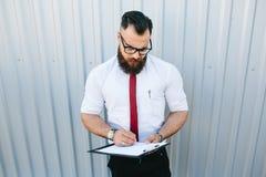 L'uomo d'affari firma un documento immagini stock