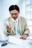 L'uomo d'affari frustrato guarda il suo telefono Fotografie Stock Libere da Diritti