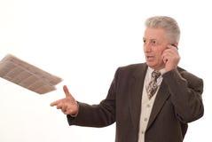 L'uomo d'affari getta un giornale su un bianco Immagine Stock