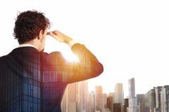 L'uomo d'affari guarda lontano per il futuro immagine stock