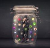L'uomo d'affari ha catturato in un barattolo di vetro con il raggiro colourful delle icone di app Immagine Stock Libera da Diritti
