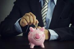 L'uomo d'affari ha messo i soldi sul porcellino salvadanaio sullo scrittorio Fotografie Stock