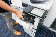 L'uomo d'affari ha messo la cartuccia di inchiostro nella stampante Fotografia Stock