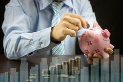 L'uomo d'affari ha messo le monete dei soldi sul raggiro sicuro e ivesting del porcellino salvadanaio, Fotografia Stock