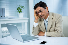 L'uomo d'affari indeciso guarda il suo computer Fotografia Stock