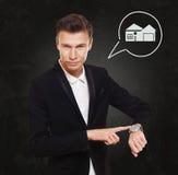 L'uomo d'affari indica all'orologio, concetto del bene immobile fotografia stock