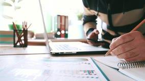 L'uomo d'affari lavora con uno smartphone ed il controllo il rapporto e dei grafici finanziari nell'ufficio nel luogo di lavoro stock footage