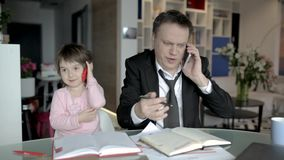L'uomo d'affari lavora dalla casa e prende la cura della sua piccola figlia video d archivio