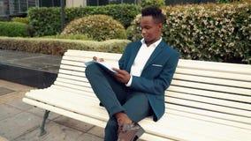 L'uomo d'affari legge i documenti o il taccuino che indossano il vestito blu vicino all'ufficio stock footage