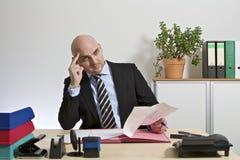 L'uomo d'affari legge meditatamente un documento Fotografia Stock
