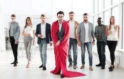 L'uomo d'affari in mantello di un superman, conduce un gruppo non decisivo di affari fotografia stock