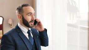 L'uomo d'affari maschio sorridente alla moda del ritratto in vestito ed il legame gesticolano e parlando facendo uso dello smartp archivi video