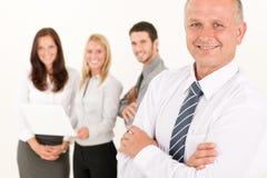 L'uomo d'affari maturo con i colleghi si leva in piedi dentro posteriore Fotografie Stock Libere da Diritti