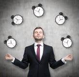 L'uomo d'affari meditativo sta riflettendo circa la gestione di tempo La persona in vestito convenzionale è circondata dalle sveg fotografia stock libera da diritti