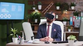 L'uomo d'affari mette una cuffia avricolare di VR e prova la realtà virtuale video d archivio