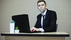 L'uomo d'affari molto si è sorpreso ed esaminando la macchina fotografica mentre lavorava ad un computer portatile nell'ufficio stock footage