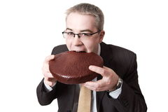 L'uomo d'affari morde il grafico a torta del cioccolato fotografia stock