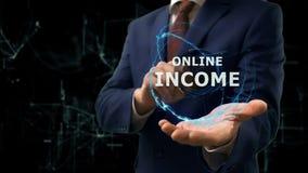 L'uomo d'affari mostra ad ologramma di concetto il reddito online sulla sua mano Immagini Stock