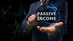 L'uomo d'affari mostra ad ologramma di concetto il reddito passivo sulla sua mano archivi video
