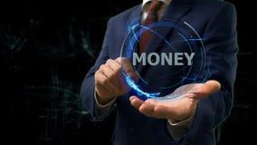 L'uomo d'affari mostra i soldi dell'ologramma di concetto sulla sua mano Immagine Stock