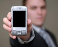 L'uomo d'affari mostra il telefono delle cellule con profondità del campo poco profonda Fotografie Stock Libere da Diritti