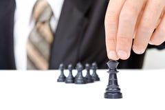 L'uomo d'affari muove la figura di re di scacchi Immagini Stock
