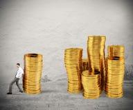 L'uomo d'affari muove un mucchio delle monete verso un gruppo di soldi concetto della difficoltà a soldi di risparmio immagine stock