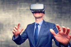 L'uomo d'affari negli occhiali di protezione d'uso di una realtà virtuale del vestito ha isolato la o immagini stock