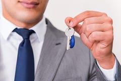 L'uomo d'affari nel concetto del bene immobile con la chiave domestica Fotografie Stock