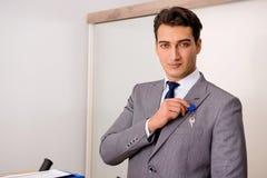L'uomo d'affari nel concetto del bene immobile con la chiave domestica Fotografia Stock