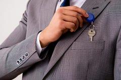 L'uomo d'affari nel concetto del bene immobile con la chiave domestica Immagini Stock