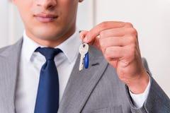 L'uomo d'affari nel concetto del bene immobile con la chiave domestica Immagine Stock